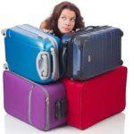 En kvinde gemmer sig bag en masse tung bagage